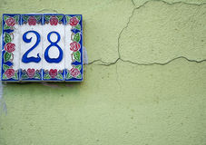 Traditional Italian home sign board painted on ceramic tile. Placed on the wall. Number twenty-eight 28 Royalty Free Stock Photos
