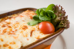 Traditional Italian lasagna, detail. Traditional Italian lasagna on the white plate with orange towel, ready to eat, detail stock photos