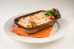 Traditional Italian lasagna. On the white plate with orange towel, ready to eat Royalty Free Stock Photo
