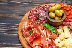 Meat and cheese plate with salami sausage, chorizo, parma and parmesan cheese. Traditional Italian meat and cheese plate with salami sausage, spanish chorizo stock photography