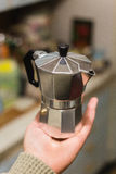 Traditional Italian moka pot coffee-maker on the hand in the kitchen Stock Photography