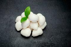 Traditional Italian Mozzarella cheese and basil on dark concrete. Background Stock Photography