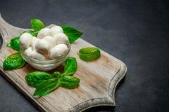 Traditional Italian Mozzarella cheese and basil on dark concrete. Background Royalty Free Stock Photo