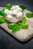 Traditional Italian Mozzarella cheese and basil on dark concrete. Background Stock Photo