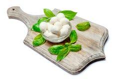 Traditional Italian Mozzarella cheese and basil on white background. Traditional Italian Mozzarella cheese and basil Isolated on white background Stock Photo