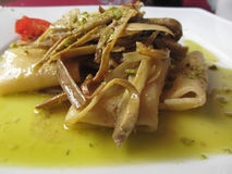 Traditional italian Paccheri pasta with artichokes and pistachios Stock Image