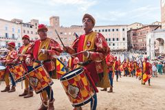 Traditional italian Palio horse race parade in Siena. Siena, Italy - June 29, 2016: Men musicians with drums in historical colorful costumes celebrating at stock images
