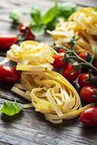 Traditional italian pasta fettuccine. Traditional uncooked italian pasta fettuccine with tomato and basil on the wooden table stock photos