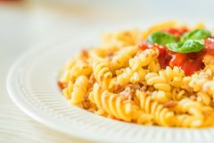 Traditional Italian pasta or fussili bolognese. Close-up of traditional Italian spaghetti or fusilli with bolognese sauce on wooden background Royalty Free Stock Images