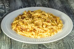 Traditional Italian pasta or fussili with mince. Close-up of traditional Italian spaghetti or fusilli with meat stuff on wooden background Royalty Free Stock Photo
