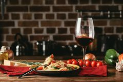 Traditional italian pasta with tomatoes and arugula in plate and glass of. Red wine royalty free stock photo