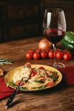 Traditional italian pasta with tomatoes and arugula in plate and glass of. Red wine royalty free stock photography