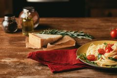 Traditional italian pasta with tomatoes and arugula in plate on wooden table with Parmesan, rosemary. And oil royalty free stock images