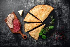 Traditional Italian pizza calzone with ingredients on a stone and dark wooden scratched background royalty free stock image