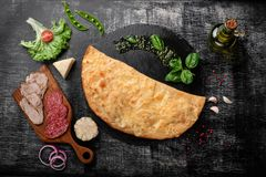Traditional Italian pizza calzone with ingredients on a stone and dark wooden scratched background stock photography