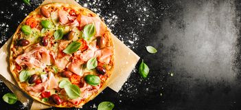 Traditional italian pizza on dark table. Top view of tasty appetizing classic italian traditional pizza with cheese, olives, basil and fresh vegetables on dark stock photography