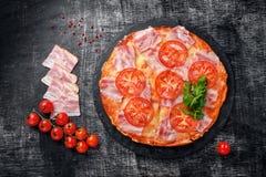 Traditional italian pizza with mozzarella cheese, ham, tomatoes royalty free stock photo