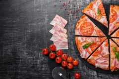 Traditional italian pizza with mozzarella cheese, ham, tomatoes, pepper, pepperoni spices and fresh rucola stock photo