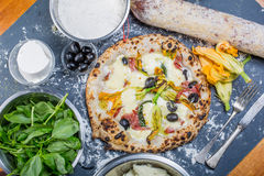 Traditional italian pizza with mozzarella, salami, ricotta and pumpkin flowers Royalty Free Stock Photography