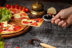 Traditional italian pizza with salami, cheese, tomatoes greens. Top view at dark stone table. Italian food background. royalty free stock photography