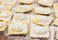 Traditional italian ravioli on cutting board. Traditional italian floured ravioli on cutting board Royalty Free Stock Photos