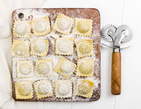 Traditional italian ravioli on cutting board. On white wooden background Stock Photography