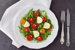 Traditional Italian salad with cherry tomato, ruccola, mozzarella, olive oil wine vinegar on a white plate on a grey Stock Image