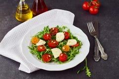 Traditional Italian salad with cherry tomato, ruccola, mozzarella, olive oil wine vinegar on a white plate on a grey Stock Photo