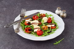 Traditional Italian salad with cherry tomato, ruccola, mozzarella, olive oil wine vinegar on a white plate on a grey Royalty Free Stock Photo