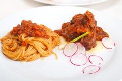 Pasta with pork ribbs sauce on polenta bed Royalty Free Stock Image