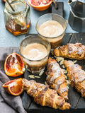 Traditional Italian style home breakfast. Latte in glasses, almond croissants and red bloody Sicilian oranges over Royalty Free Stock Photography