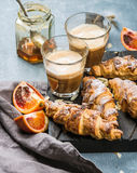 Traditional Italian style home breakfast. Latte in glasses, almond croissants and red bloody Sicilian oranges over Royalty Free Stock Images