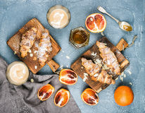 Traditional Italian style home breakfast. Latte in glasses, almond croissants on rustic wooden boards and red bloody Royalty Free Stock Image