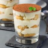 Traditional italian Tiramisu dessert cake in a glass, decorated stock photography