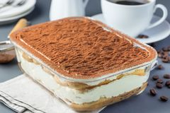 Traditional italian Tiramisu dessert cake in a glass form, decorated with cocoa powder with coffee cup, on a gray background,. Horizontal royalty free stock photos