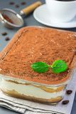 Traditional italian Tiramisu dessert cake in a glass form, decorated with cocoa powder, mint and coffee beans on a gray background. Vertical, closeup royalty free stock photo