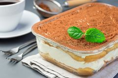 Traditional italian Tiramisu dessert cake in a glass form, decorated with cocoa powder and mint, with coffee cup, on a gray. Background, horizontal stock images