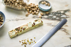 Traditional Italian Torrone. Nougat on kitchen surface next to pistachio nuts Royalty Free Stock Photos