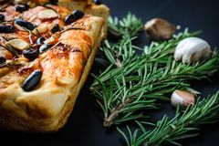 Traditional Italian vegetarian focaccia of homemade bread with olives, rosemary and garlic Royalty Free Stock Image