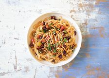 Traditional Itallian pasta spaghetti alla puttanesca. With anchovies, tomatoes, olives, capers, garlic and parsley. Top view stock photos