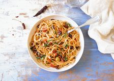 Traditional Itallian pasta spaghetti alla puttanesca. With anchovies, tomatoes, olives, capers, garlic and parsley. Top view royalty free stock photo