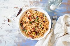 Traditional Itallian pasta spaghetti alla puttanesca. With anchovies, tomatoes, olives, capers, garlic and parsley. Top view stock image