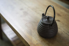 Traditional japanese black teapot on wood table Royalty Free Stock Photos