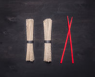 Traditional Japanese buckwheat soba noodles with red chopsticks laid out in a row on wooden rustic background top view close up Royalty Free Stock Photography
