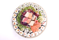 Traditional Japanese food. Composition of rolls, fish and vegetables served on the round plate royalty free stock photo