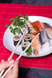 Traditional japanese food - sushi. Hand over Royalty Free Stock Photo