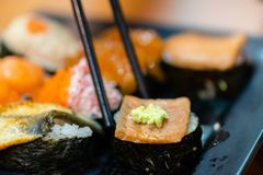 Traditional japanese local food sushi.delicious seafood sushi with wasabi and seaweed on black plate.japanese chef cook sushi for. Customer at japanese royalty free stock images