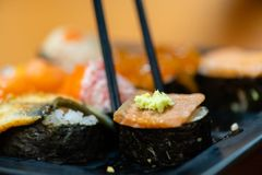 Traditional japanese local food sushi.delicious seafood sushi with wasabi and seaweed on black plate.japanese chef cook sushi for. Customer at japanese royalty free stock photos
