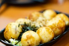 Traditional japanese local food takoyaki.delicious seafood takoyaki with seaweed on black plate.japanese chef cook takoyaki for. Customer at japanese restaurant royalty free stock image