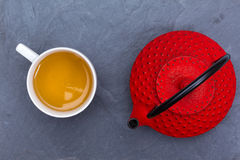 Traditional Japanese red teapot and a cup of tea. Traditional Japanese red teapot and tea on black slate Royalty Free Stock Photography